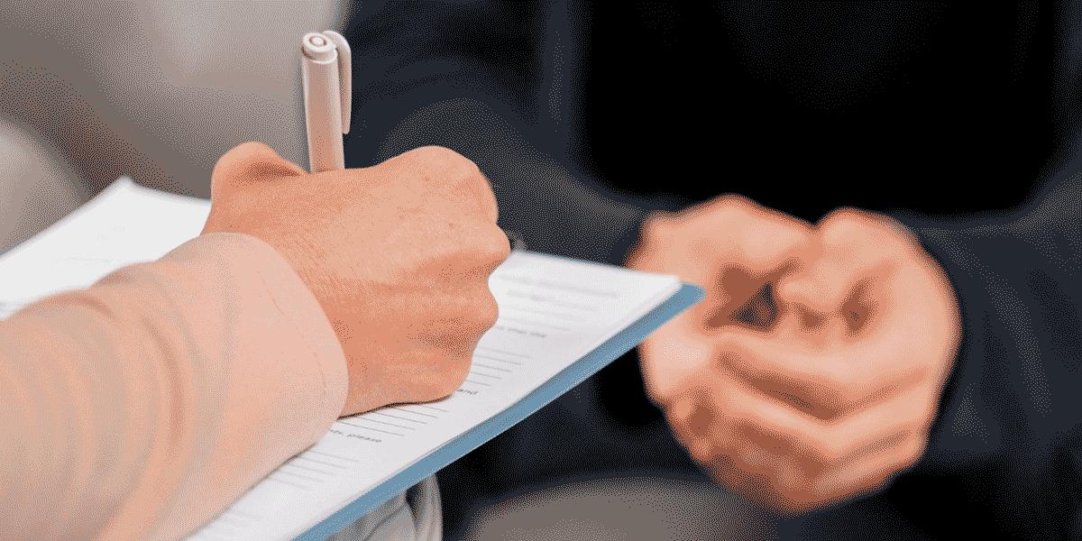 mãos escrevendo em uma prancheta durante teste vocacional