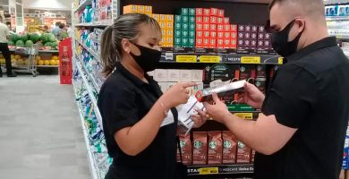 mulher mostrando produto para homem em supermercado em uma ação promocional