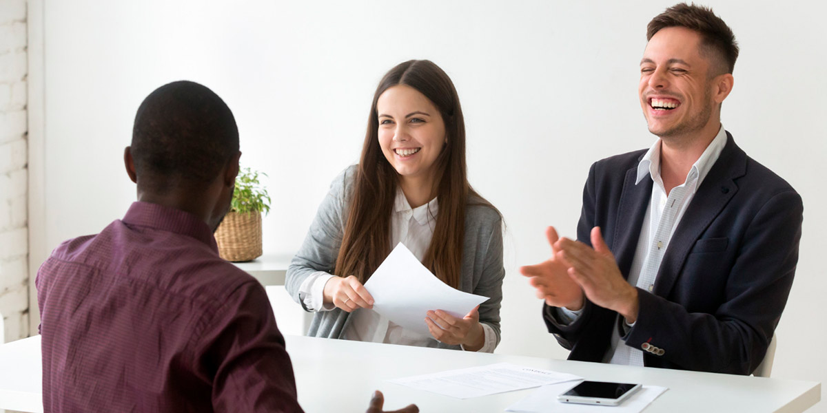 casal de executivos entrevistando candidato a vaga por processo de recrutamento e seleção de pessoas