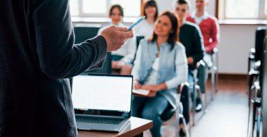 equipe de colaboradores sentada em sala de aula recebendo treinamento corporativo