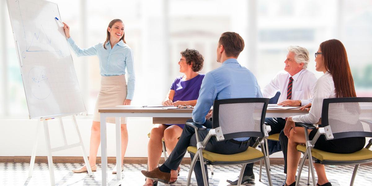 equipe de colaboradores sentada em sala de reunião recebendo treinamento corporativo de uma mulher