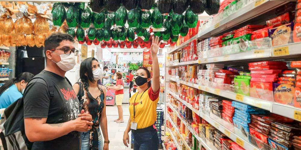 promotora de vendas em ação promocional informando oferta de ovos de Páscoa para consumidores de supermercado