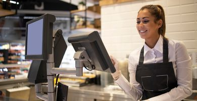atendente de caixa sorrindo após sua contratação de mão de obra terceirizada