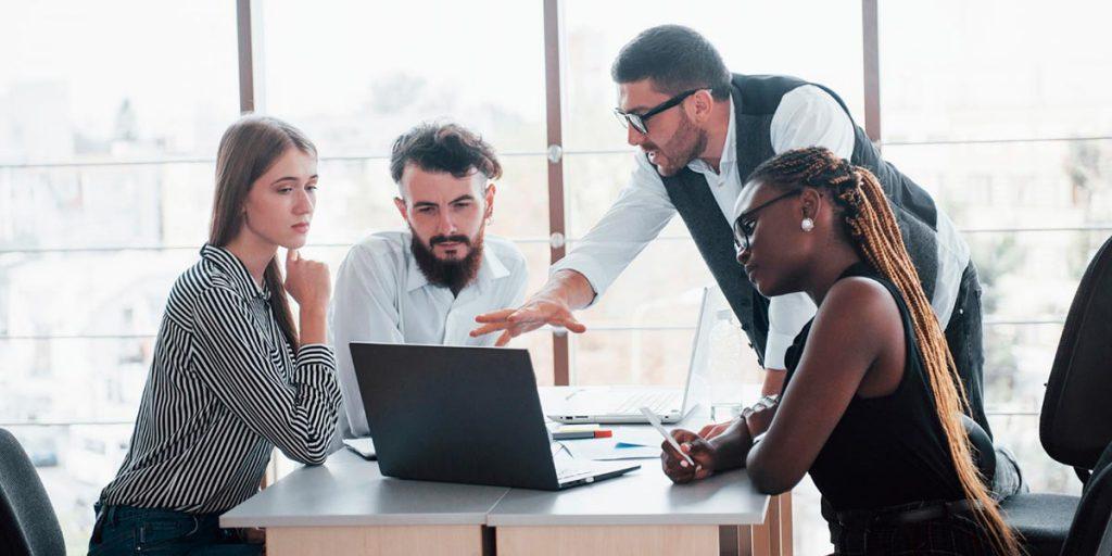 homem orientando três colaboradores em escritório aplica a gestão estratégica de pessoas para ter uma equipe de sucesso