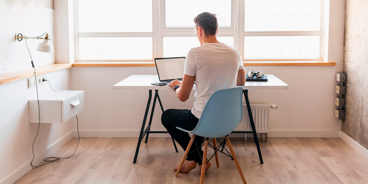 homem sentado em home office trabalhando no computador por causa da pandemia de covid-19
