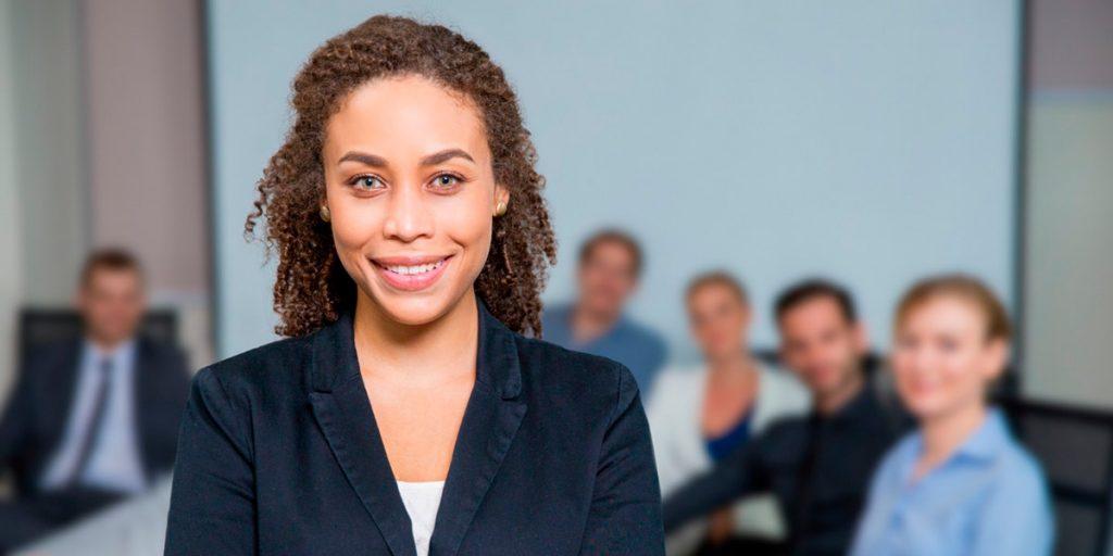 mulher a frente de mesa em reunião aplica a gestão estratégica de pessoas para ter uma equipe de sucesso