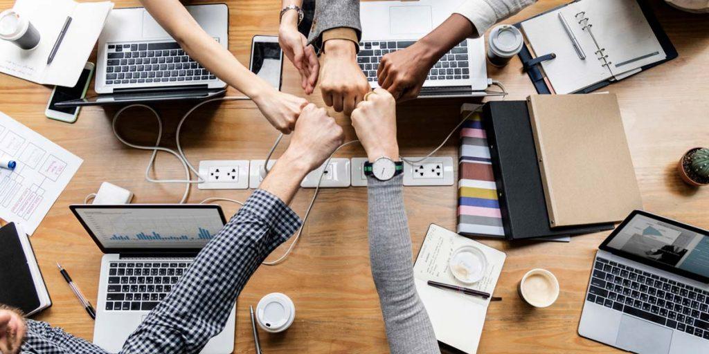 Colaboradores fazendo cumprimento de união em empresa que sabe como motivar a equipe