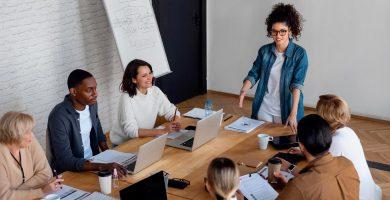 gestora e colaboradores em sala de reunião sabe como motivar a equipe