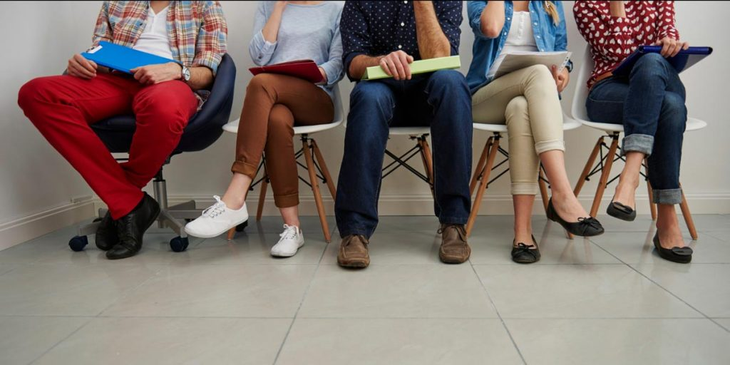várias pessoas sentadas esperando entrevista em empresa de recrutamento e seleção